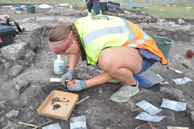 Clara Alfsdotter frilägger skelettdelar i utgrävningsschaktet.