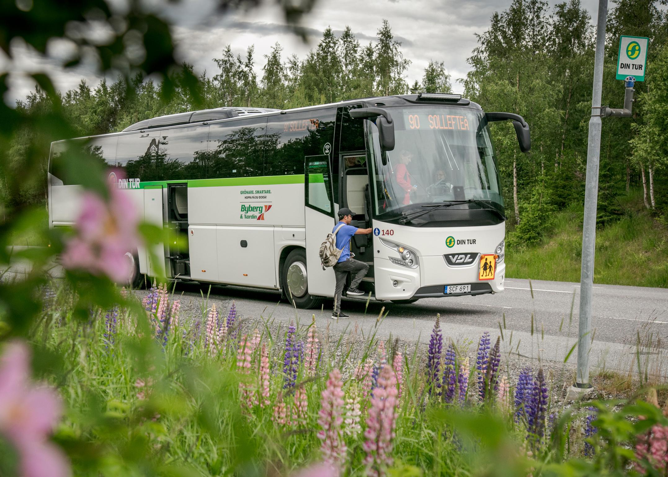 Bild på en landsbygdsbuss vid en hållplats.