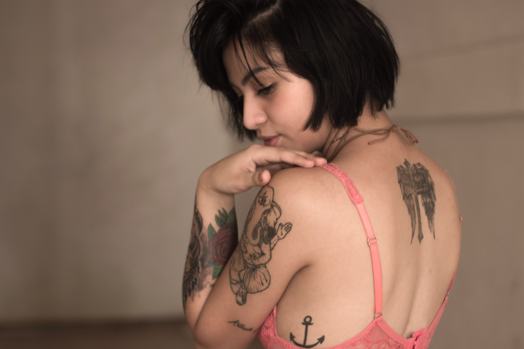 A tattooed woman wearing a bra and looking over her shoulder