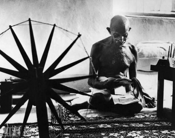 Махатма Ганди рядом со своей прялкой, которая считалась символом ненасильственного движения за независимость Индии