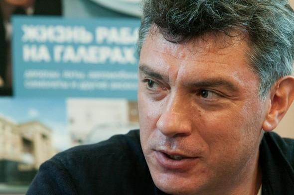 Борис Немцов на фоне плаката своего доклада о В. Путине «Жизнь раба на галерах. Дворцы, яхты, автомобили, самолёты и другие аксессуары» (2012 г.)